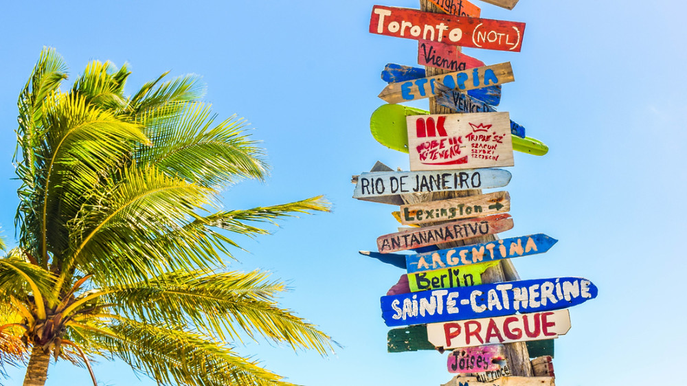 a collection of tourist destinations sign posted on the beach
