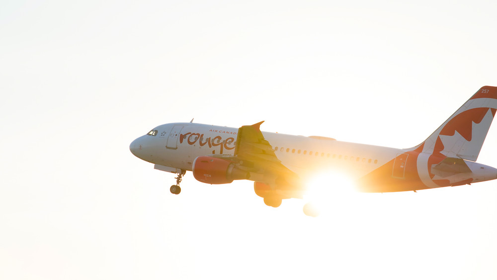 Air Canada Rouge flies in front of the sun