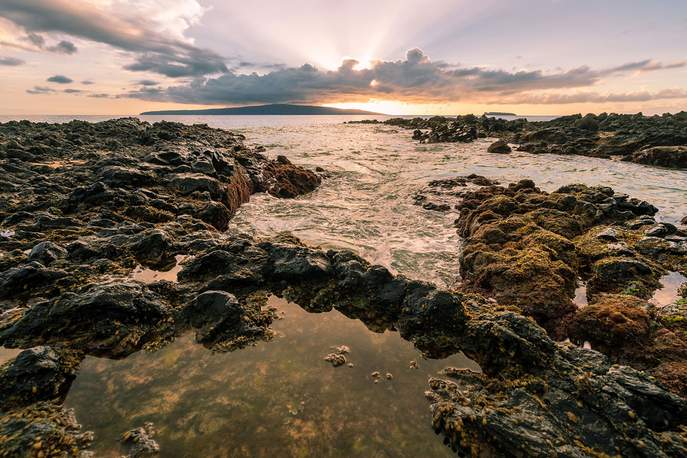 Sun over sea and rock at Maui's Makena Cove