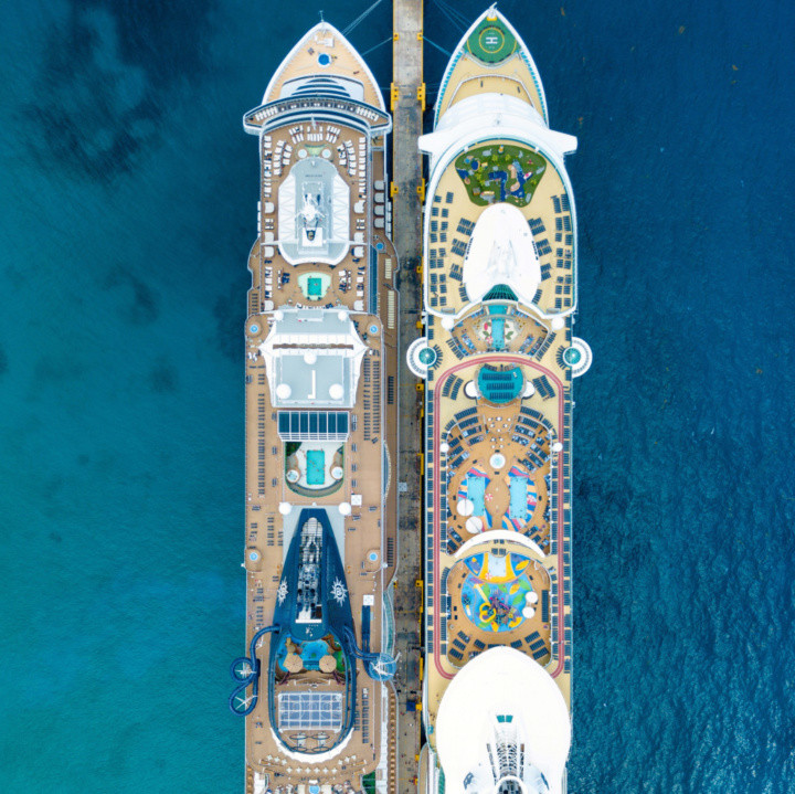Two cruise ships side by side in port as seen from a drone