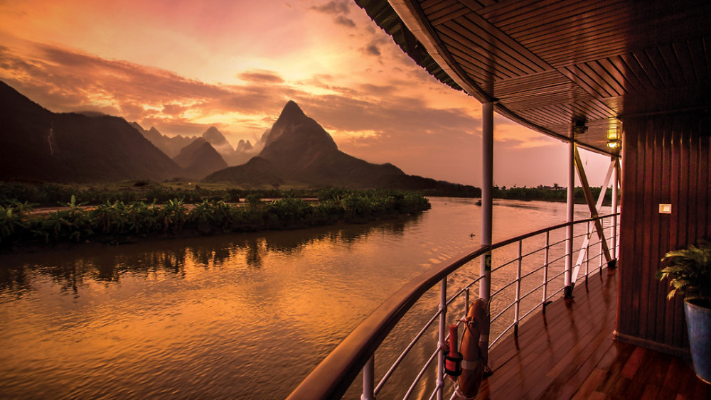 Sunset over karst landscape of Southeast Asia from river cruise ship Pandaw Expeditions