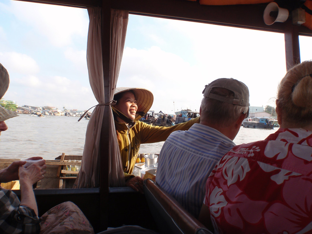 A woman sells refreshments to tourists by boat in a floating market on the Mekong in Vietnam, just west of Ho Chi Minh