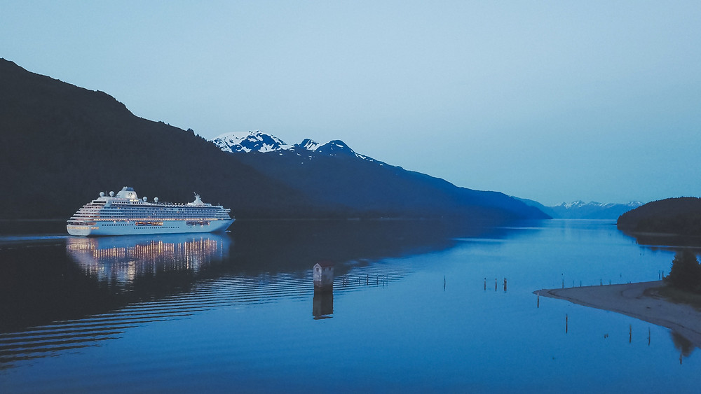 Crystal Serenity cruise ship sailing reflective waters of Juneau in Alaska