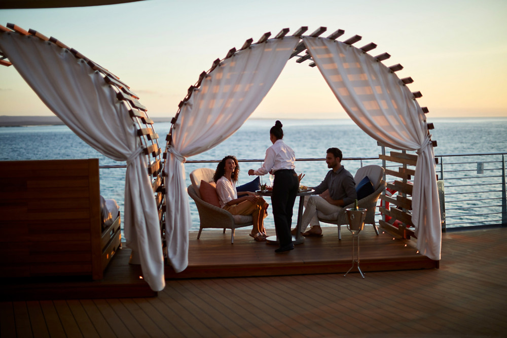 A couple makes their drinks order in a private cabana on the top deck of the Celebrity Flora before setting up for a night of glamping