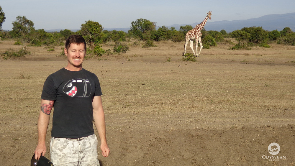 man with closed eyes poses with a wild giraffe in the background