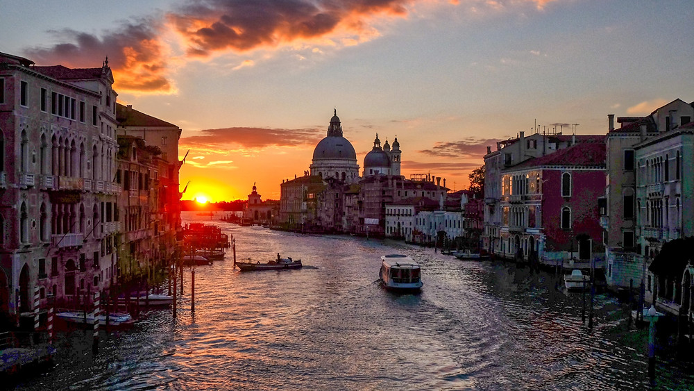 The sun rising over the canals of Venice, Italy. Boats on the water and the grand domes of a cathedral in the background