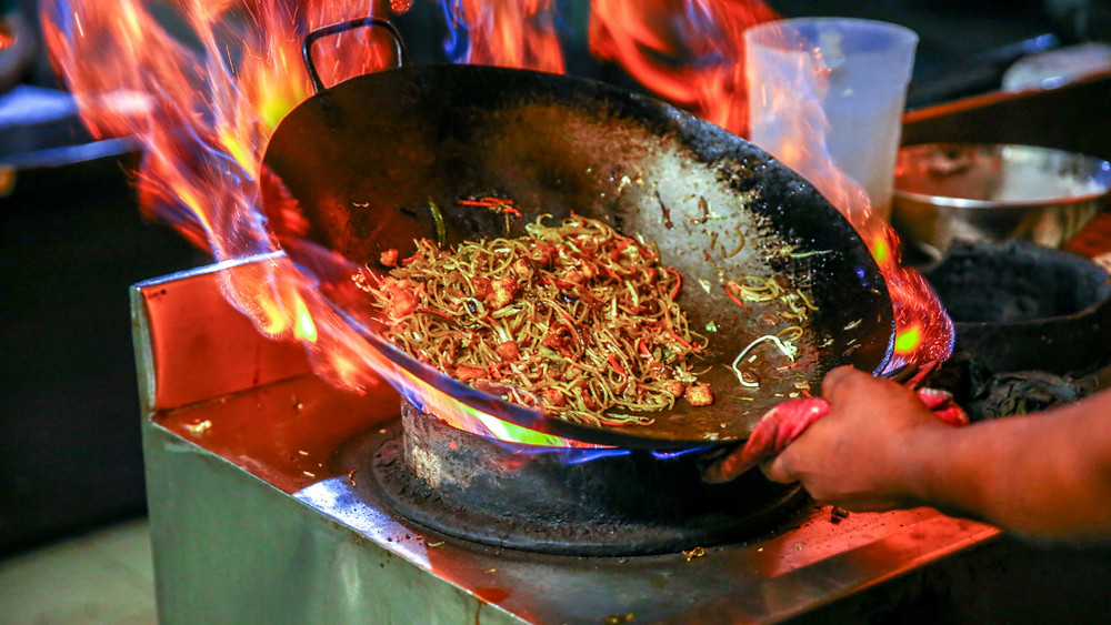 A large flame heats a wok of fresh chilis and ingredients for delicious Thai food on the streets of Thailand