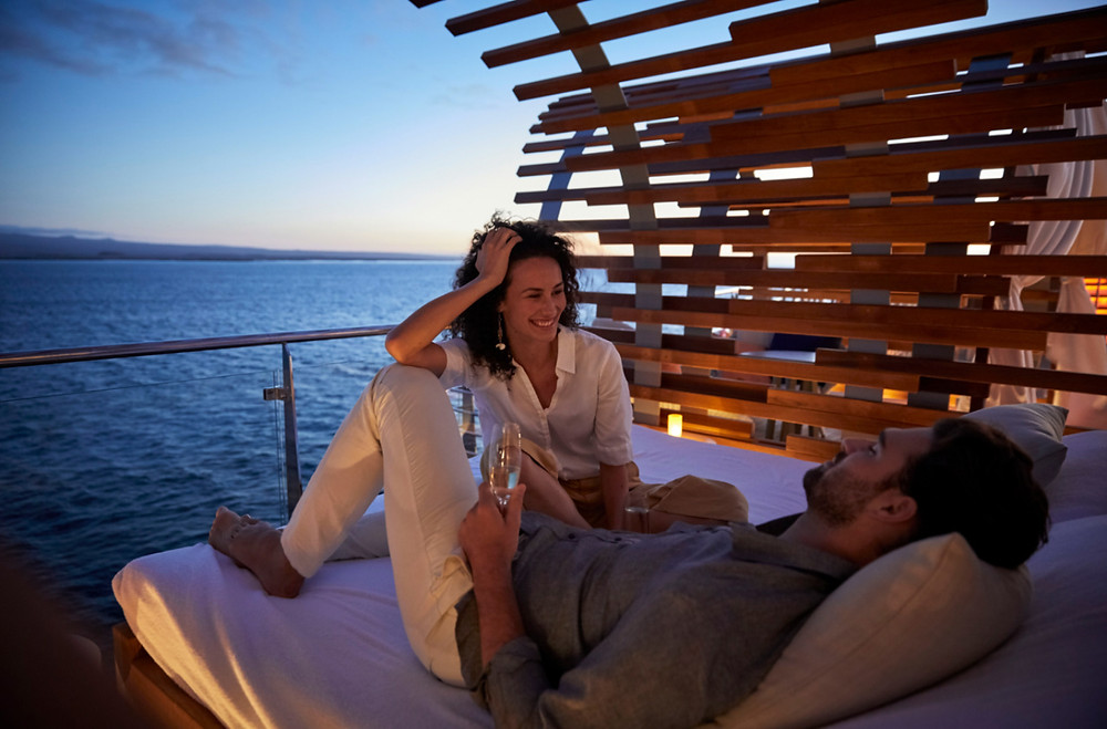 couple enjoying a glamping experience under the stars in a private cabana on board Celebrity Fora in the Galapagos Islands