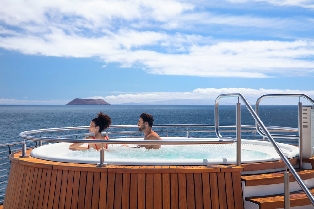 Couple in a hot tub on deck of the Celebrity Flora after exciting shore excursions