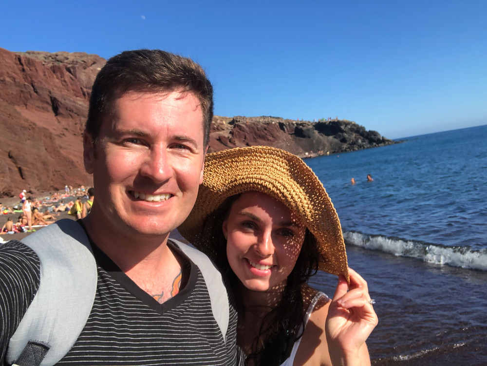 A young couple on a romantic vacation to Santorini on Red Beach