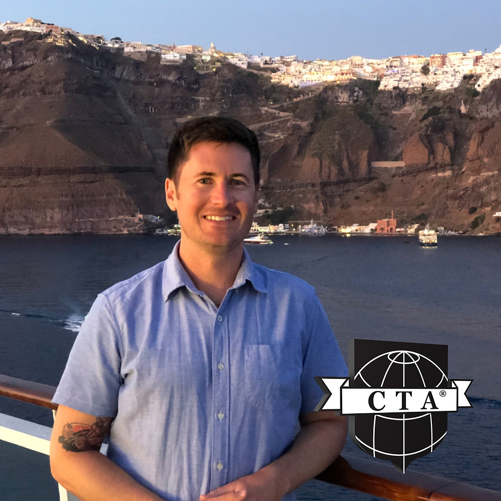 Certified Travel Associate Shy onboard a cruise ship in Santorini, overlooking Thira and showcasing the CTA designation from The Travel Institute