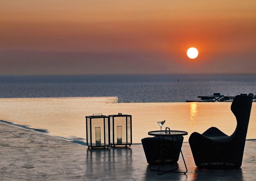 The sun setting over Santorini and the infinity pool at Santo Maris Oia Luxury Suites & Spa