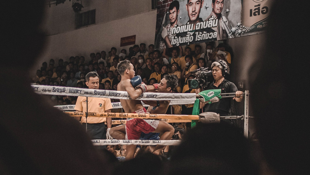 Muay Thai boxing match in Thailand as seen from between the heads of other spectators