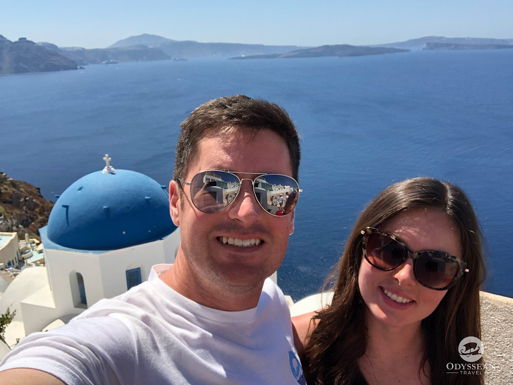 A young couple celebrate a romantic trip to Santorini in Greece. Blue domed church, blue sea and sky in the background