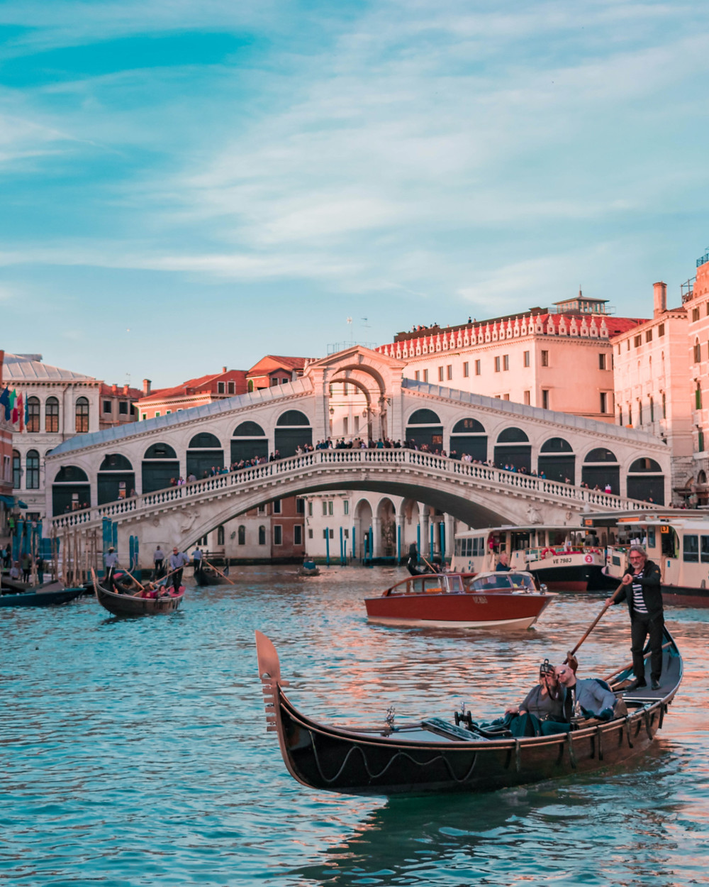 Tourists on a gondola in Venice near the Rialto Bridge