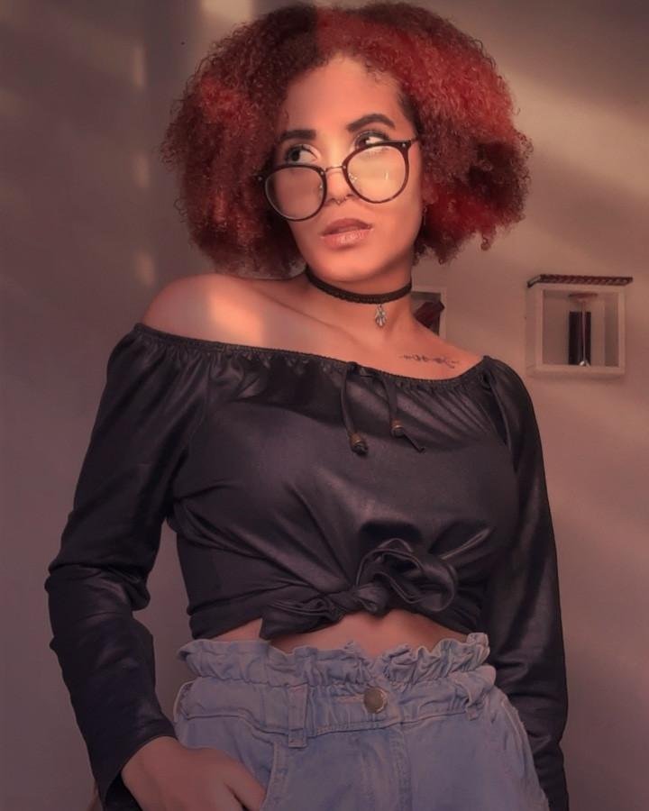 Foto da escritora Nia: uma mulher de 20 anos, cabelos cacheados, pele da cor negra, com óculos, uma blusa preta com mangas longas, calça jeans, uma gargantilha. Ela está em frente a uma parede branca com dois enfeites e parece que o sol toca o rosto dela pela janela.