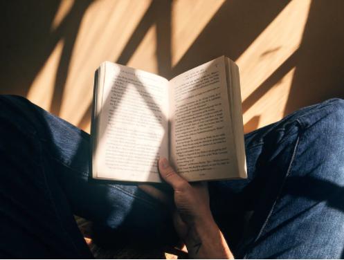 Pessoa lendo um livro em baixo de uma janela ensolarada.