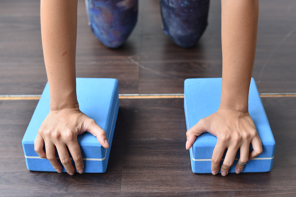 hands grabbing Yoga blocks as a modification to do Yoga when wrists are painful