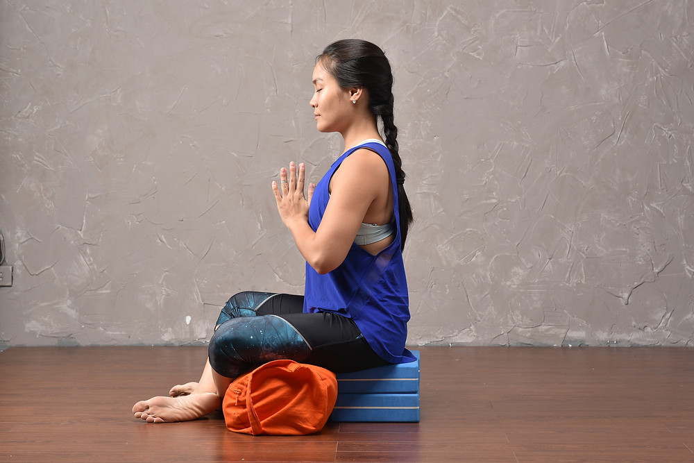 practice Yoga in sitting pose for meditation, using blocks and bolsters.