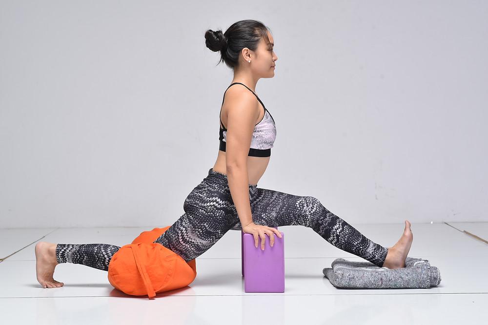 Ha My Yoga Sweden practicing front split hanumanasana using props: blocks, bolster, blanket