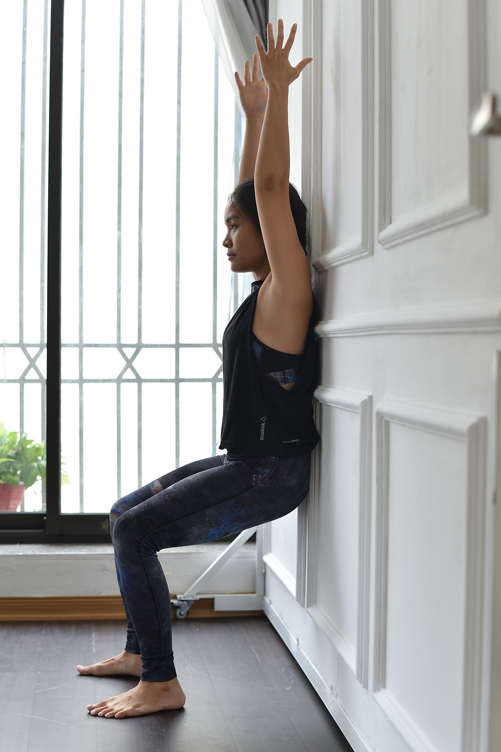 Ha My Yoga teacher in Malmö Sweden is doing chair pose in Yoga with a wall
