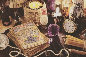 tarot cards, candles, watch, pearls, crystals