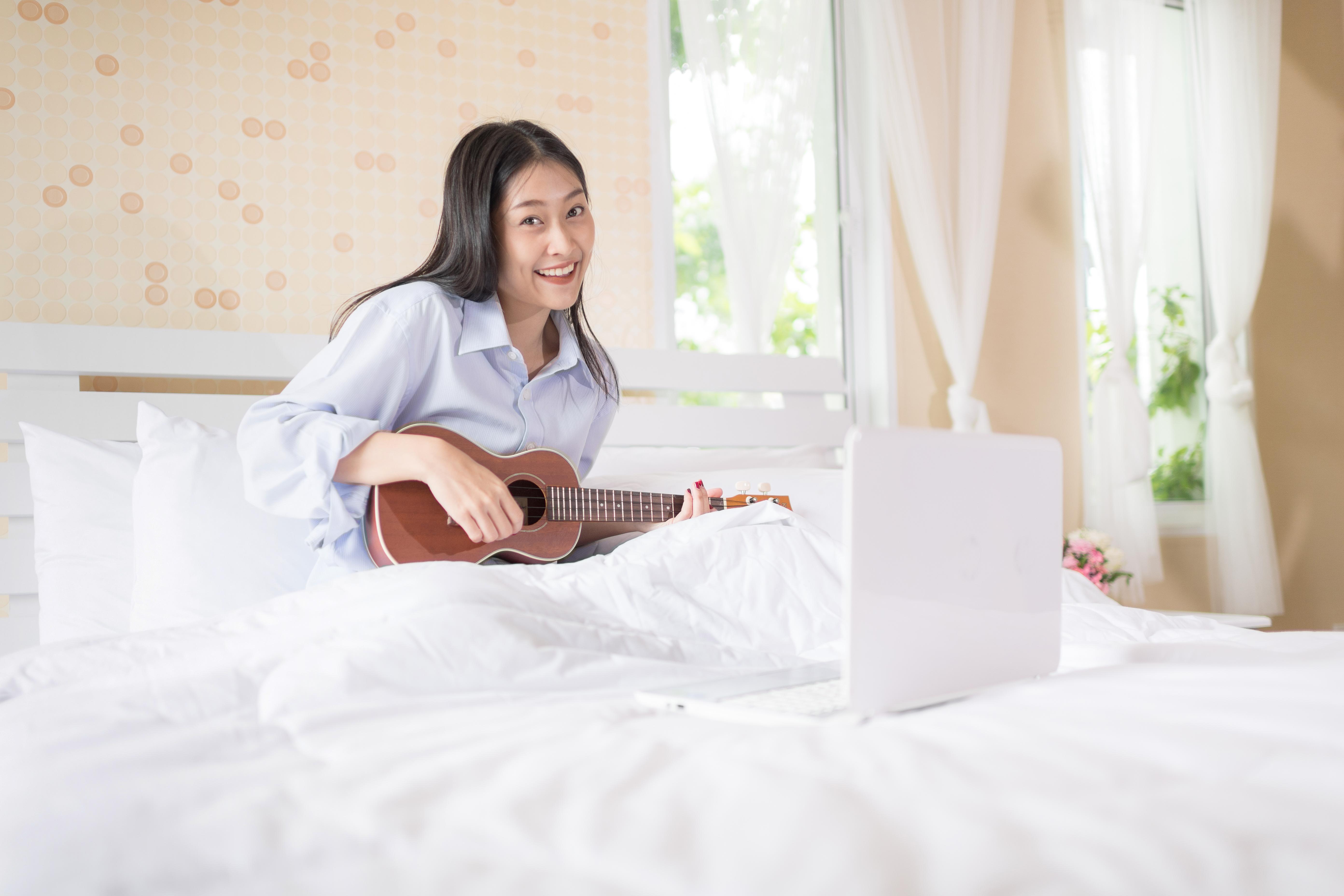 Beautiful girl practice playing ukulele