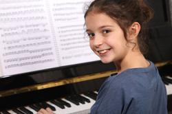 Girl playing piano - Fishers Guitar