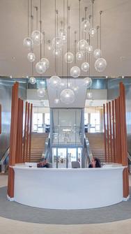 Placé au centre de l'espace et mis en valeur pas le grand lustre qui le surplombe, le comptoir d'accueil marque la première étape des visiteurs qui pénètrent dans le hall d'entrée de l'Hôtel de ville.