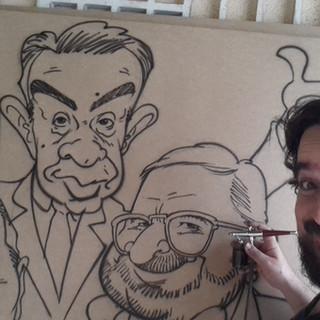 Edu produzindo painéis com caricaturas em encontros improváveis