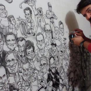 Edu pintando quadro com 75 caricaturas