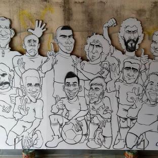 Painel modulado (dobrável) com 2,75 X 1,80 m com a pintura das caricaturas de 12 jogadores da Seleção Brasileira - antes de receber cores