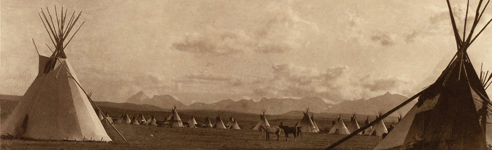 Piegan tipis dot the landscape with Glacier National Park mountains behind them.