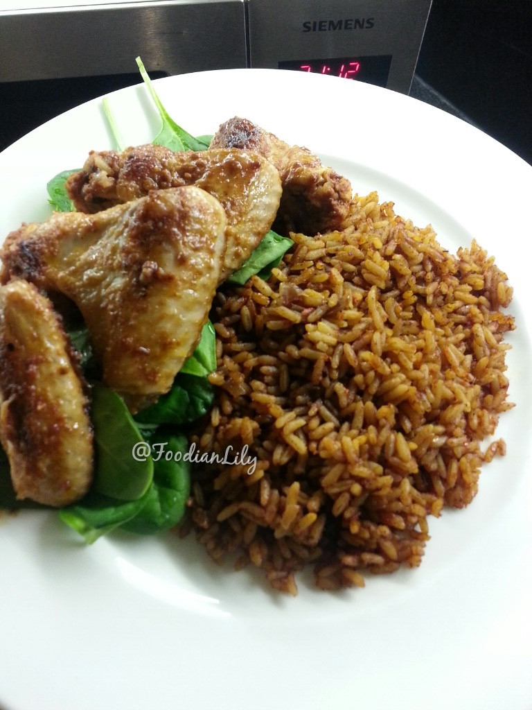 Jollof rice with chicken wings on a bed of spinach