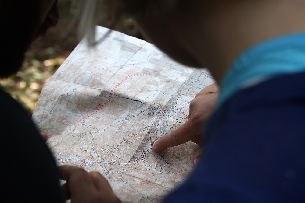 Hikers looking at trail map outdoors during hike