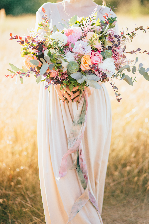 big wedding bouquet in hands of the bride