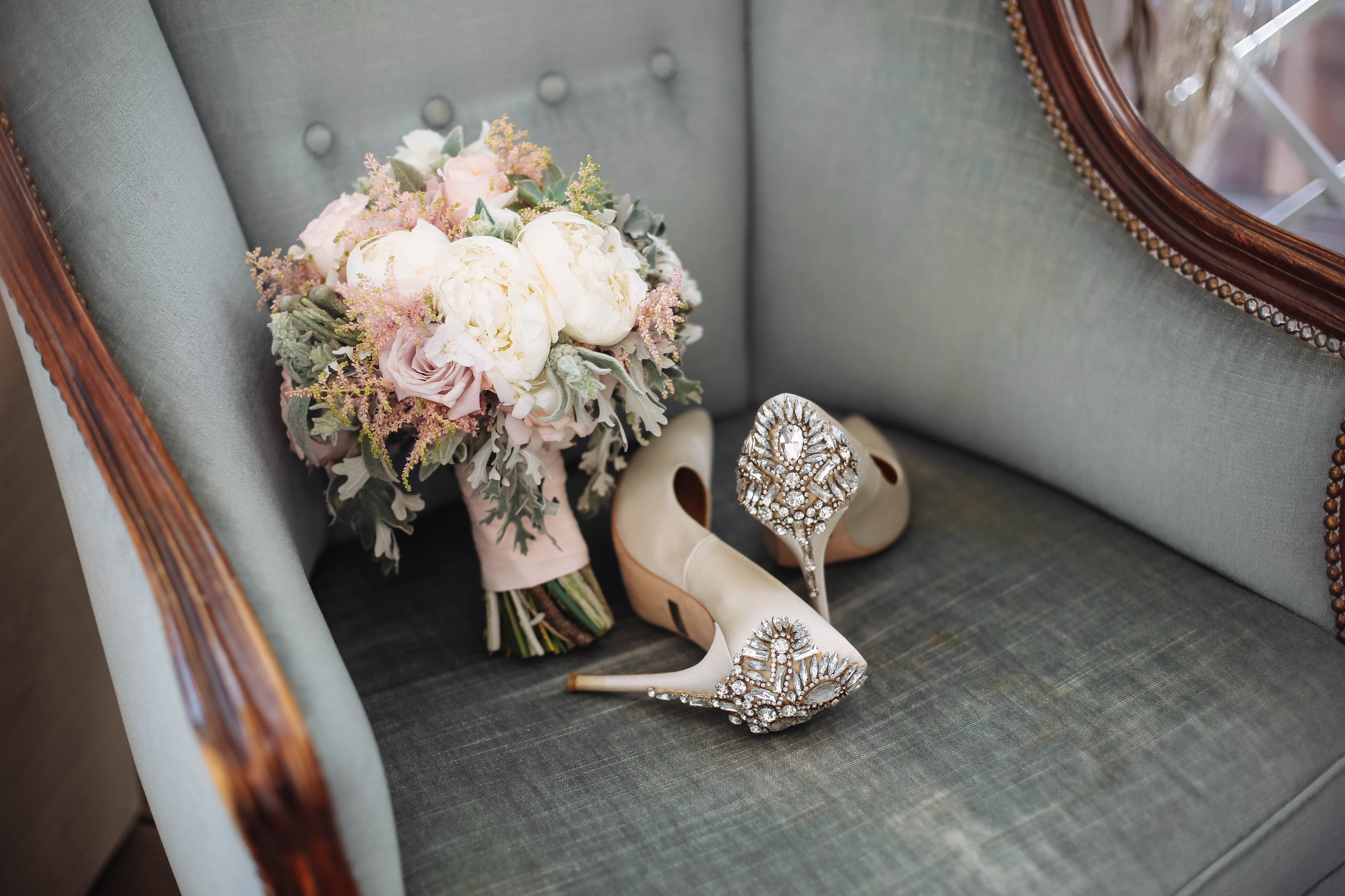 Brides wedding shoes with a bouquet with roses and other flowers on tha arm chair