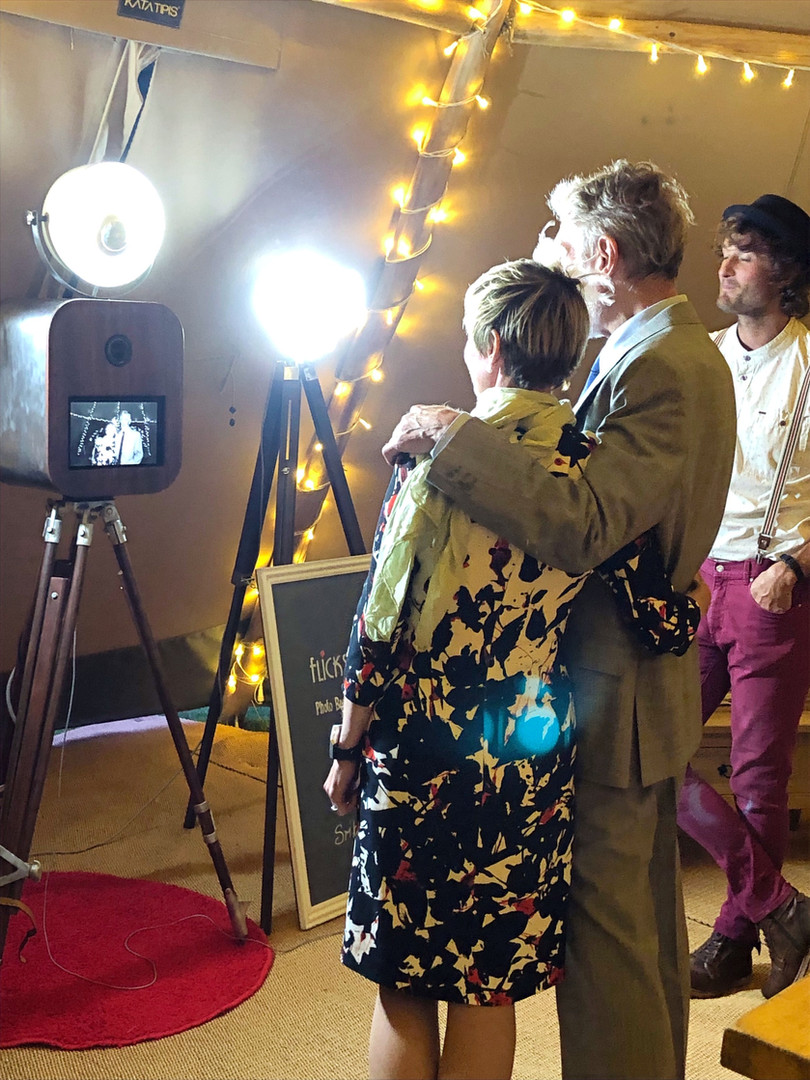 Couple taking photos in tipi photo booth near Rock