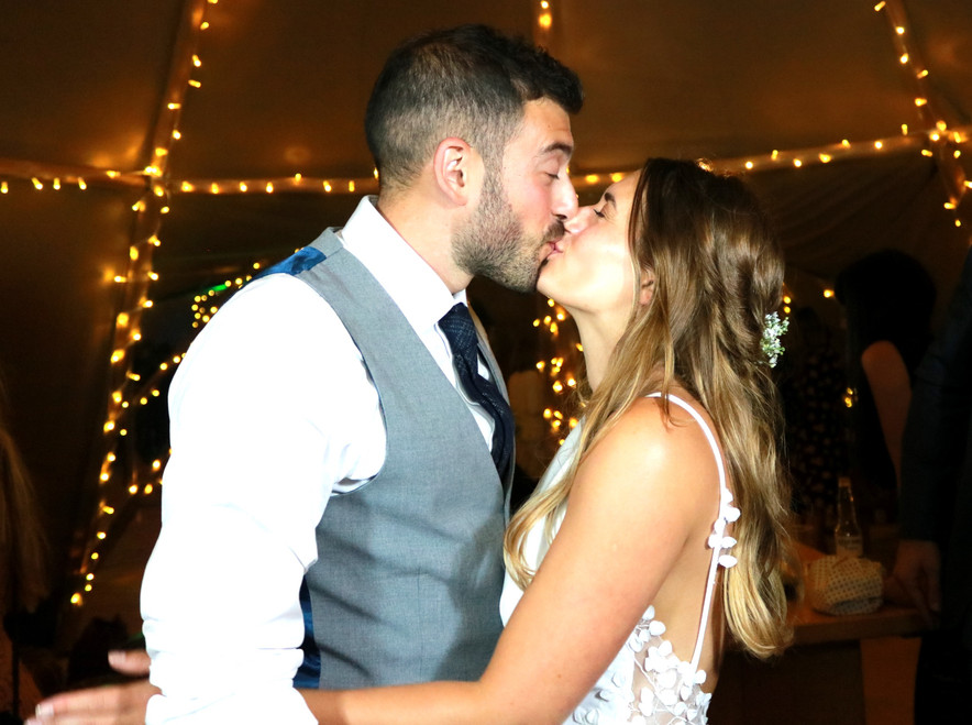 photo booth shot of bride and groom kissing in tipi