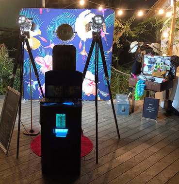 photo booth set up with tropical backdrop