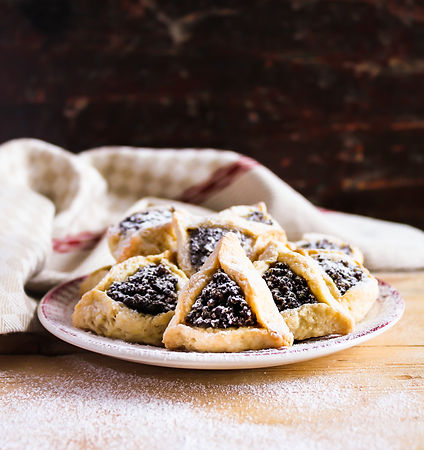 Hamantaschen cookies with poppy seed and dried fruits filling and icing sugar on a plate, cooked for