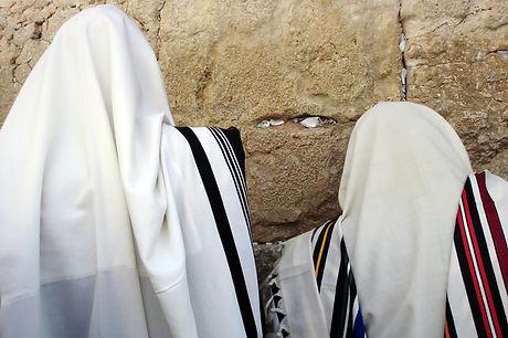 Jewish Men are praying wrapped in talit