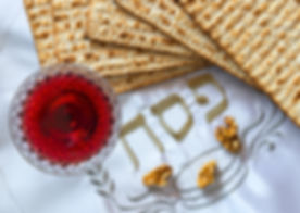 Traditional food (matzah) and drink (red wine) for Jewish Passover Holiday, placed on a white festiv