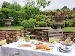 Patio seating overlooks manicured gardens - Lea Hall, Matlock