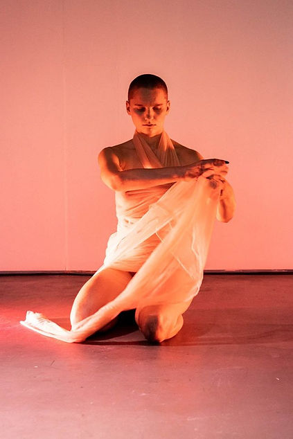 A bald performer wraps her body around with a light yellow fabric. The performer is sitting on the floor and behind her there's a pink wall. The performer is lit with soft yellow and pink lights.