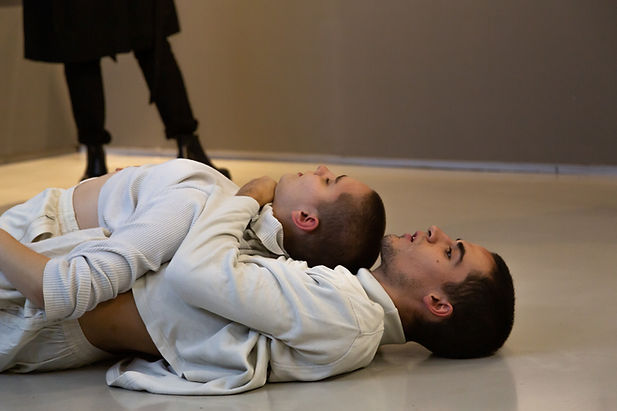 Two bald people wearing white clothes are lying on the white gallery floor. One person is lying on top of the other, while the other person is embracing the one on top. One person has their eyes closed.