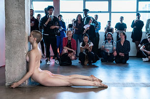 A naked dancer performs in front of a crowd of people in an industrial space. The dancer touches her chest to the column and her legs are resting on the floor.