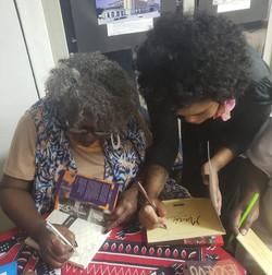 Ao lado de Conceição Evaristo, trocando autógrafos