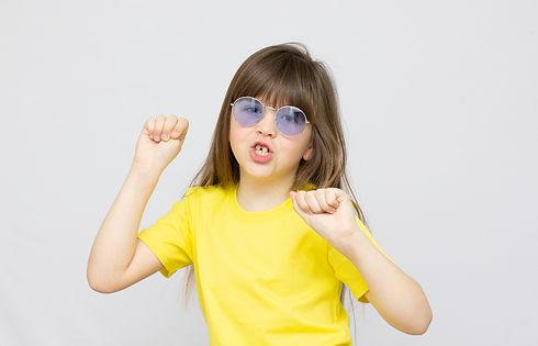 photo-brunette-hairdo-impressed-little-girl-dance-wear-blue-sunglasse-yellow-t-shirt-backg
