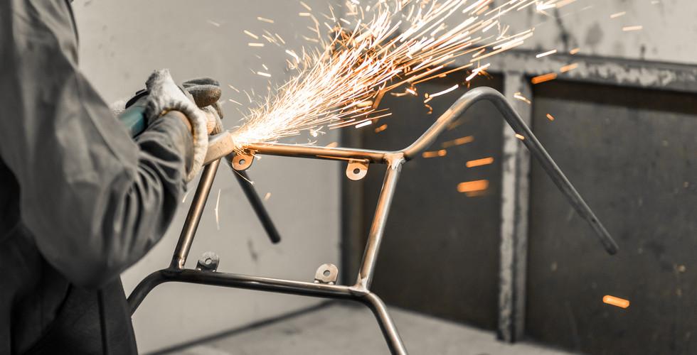 worker in furniture factory grinding met